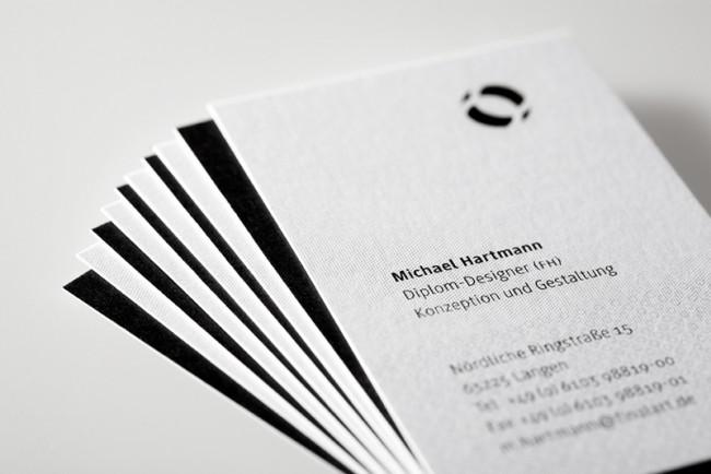 Eine gelaserte Bildmarke, die ein abstrahiertes Auge darstellt und durch ihre »Öffnung«  die Vielfalt der  Visitenkarten-Umgebung einbezieht
