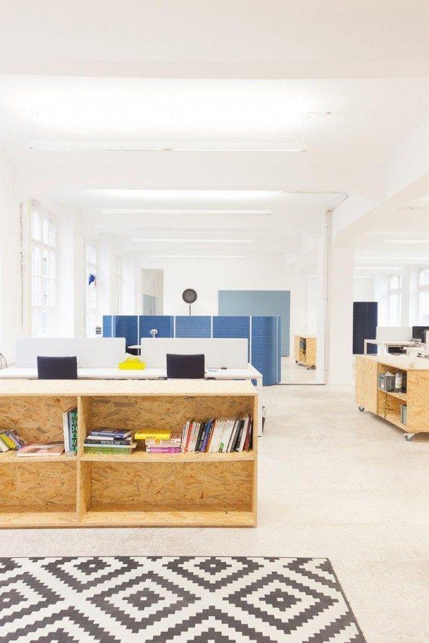 Die blauen Trennwände im Hintergrund beinhalten auf jeder Seite eine kleine Nische mit zwei Sitzplätzen für spontane Meetings