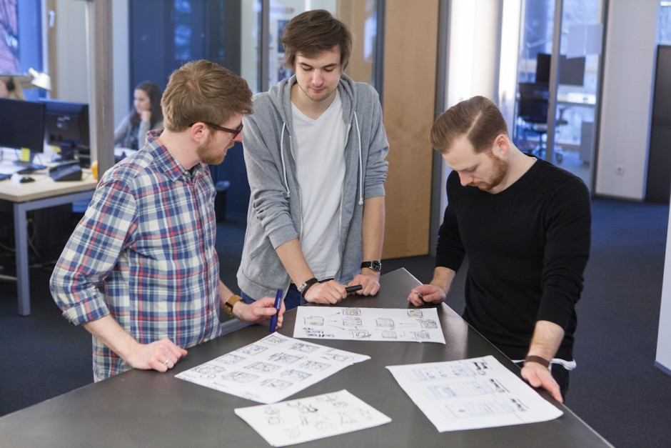 Die Interaction Designer Daniel Kränz (links) und Fabian Orthen (rechts) besprechen gemeinsam mit Interaction-Design-Praktikant Lucas Köhler erste Entwürfe zur Informationsarchitektur.