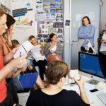 Das Team berät sich in der Projektecke, wo die Entwürfe für kommende Geschichten die Wände säumen