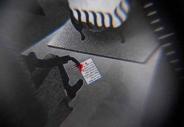 Die Auflösung findet man im Mikrotext auf der Notiz in der Hand des Mannes. (Detail)