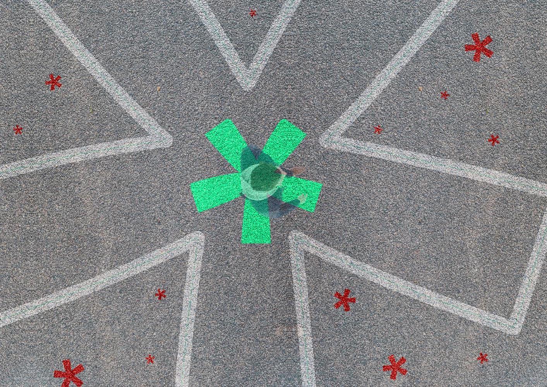 Asterisk auf Asphalt mit Person im Zentrum