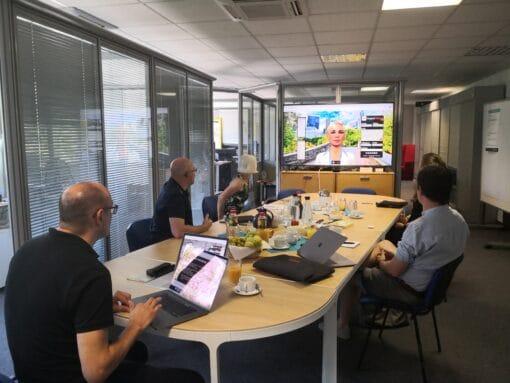 Konferenzraum mit Menschen und Leinwand mit Avatar