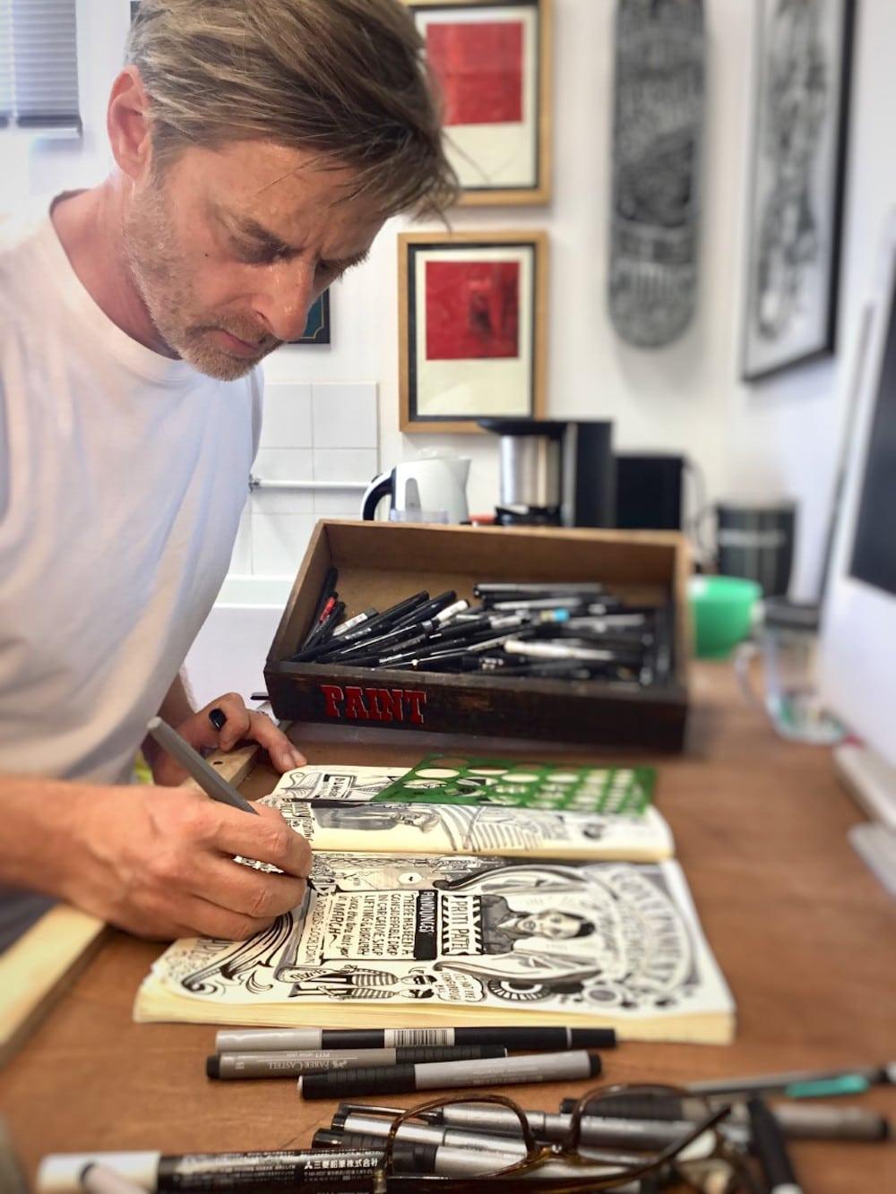 Illustrator Vic Lee in seinem Londoner Atelier, man sieht wie er an seinem Corona Diary zeichnet