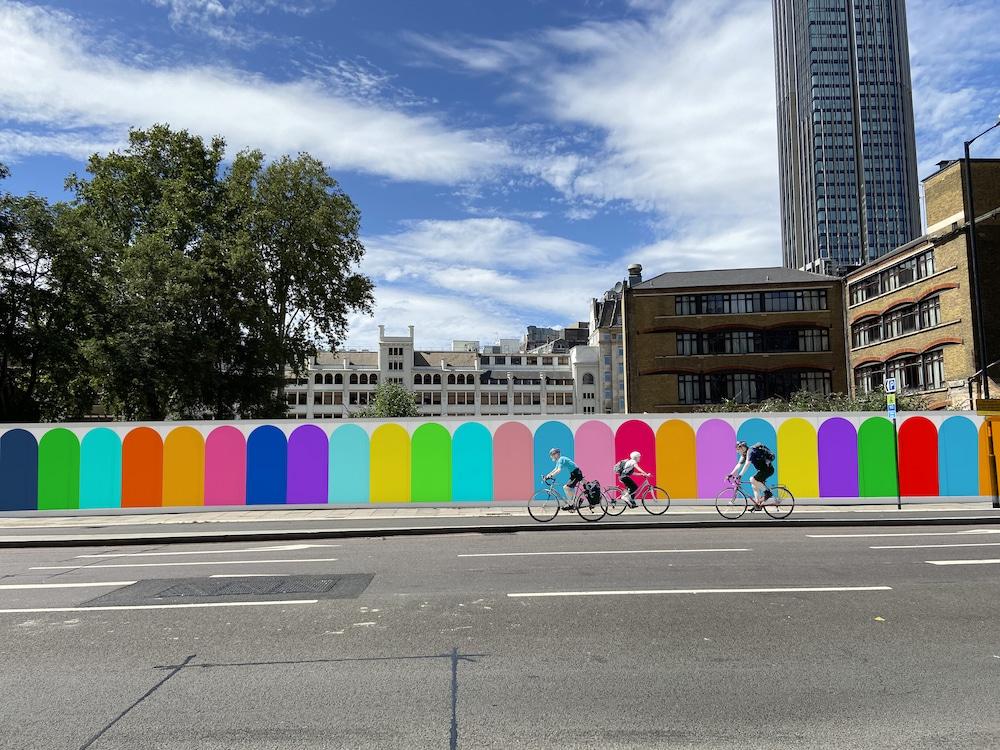 Bunter Zaun mit Fahrradfahrern